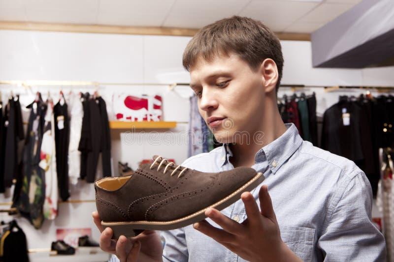 Mens die schoenen kiezen tijdens schoeisel die bij schoenwinkel winkelen royalty-vrije stock foto's