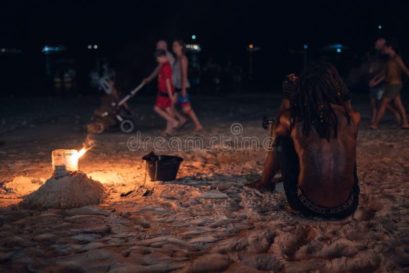 Mens die schommeling van brandslinger tonen op het strand royalty-vrije stock afbeeldingen