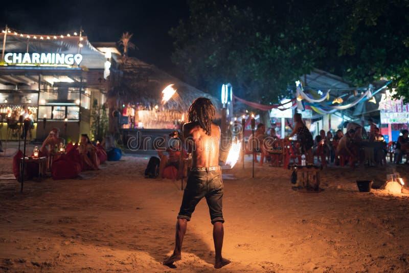 Mens die schommeling van brandslinger tonen op het strand royalty-vrije stock foto