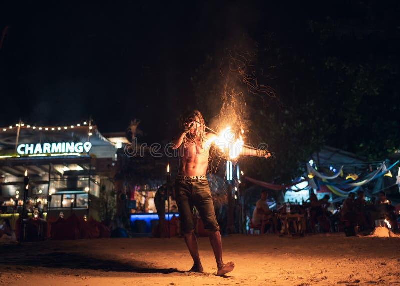 Mens die schommeling van brandslinger tonen op het strand stock foto