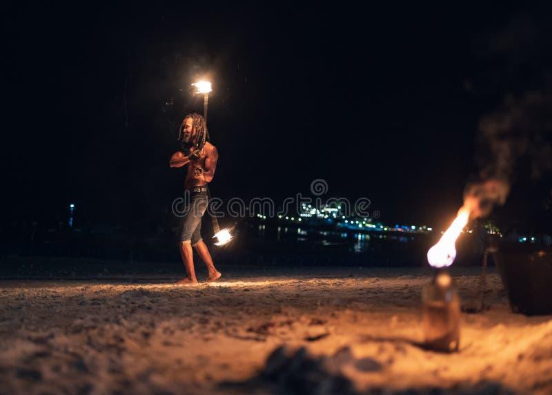 Mens die schommeling van brandslinger tonen op het strand stock fotografie