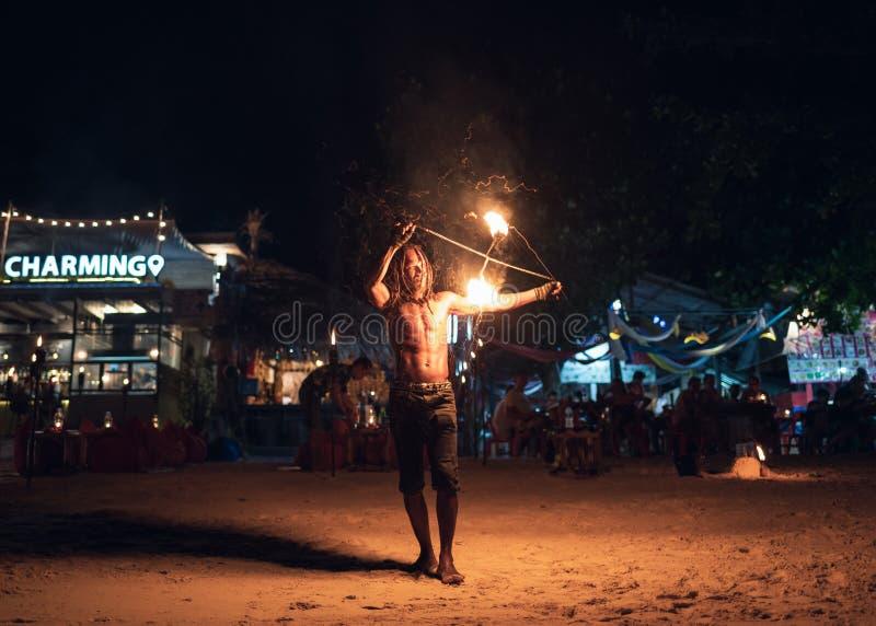 Mens die schommeling van brandslinger tonen op het strand royalty-vrije stock afbeelding