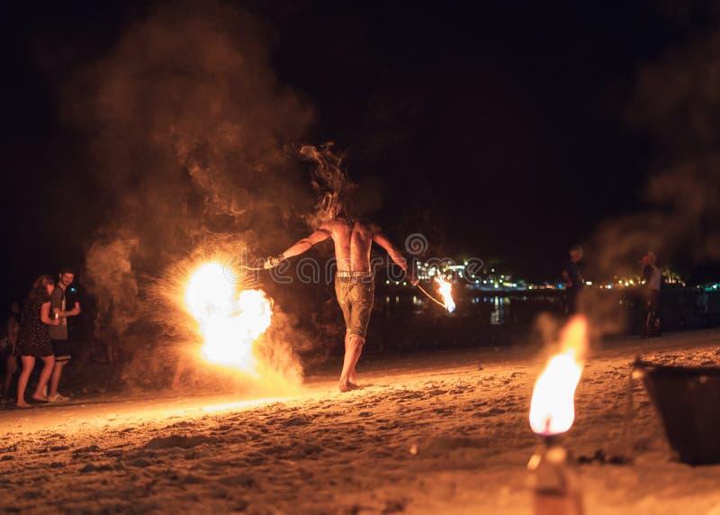 Mens die schommeling van brandslinger toont op het strand royalty-vrije stock afbeelding