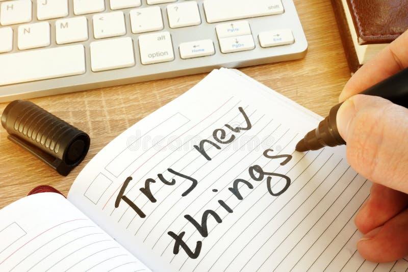 Mens die schrijven: probeer nieuwe dingen in een nota stock afbeeldingen
