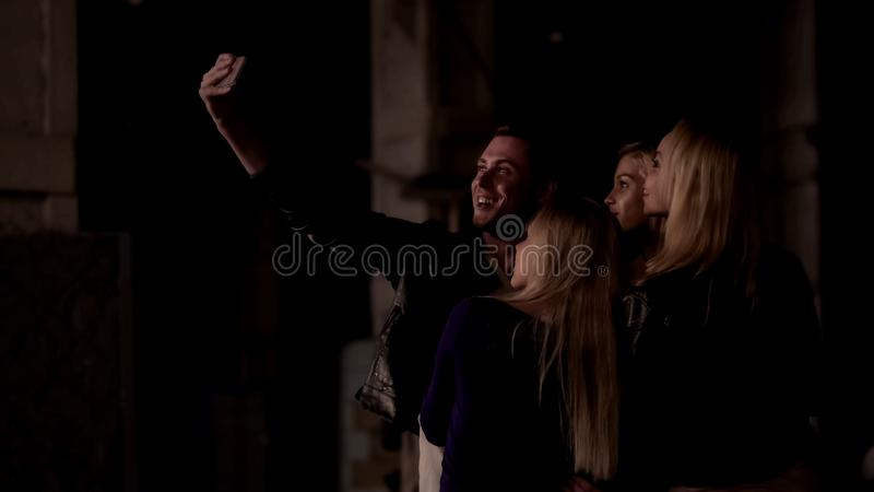 Mens die selfie met mooie meisjes nemen om goede tijd te herinneren samen, nachtleven royalty-vrije stock afbeeldingen