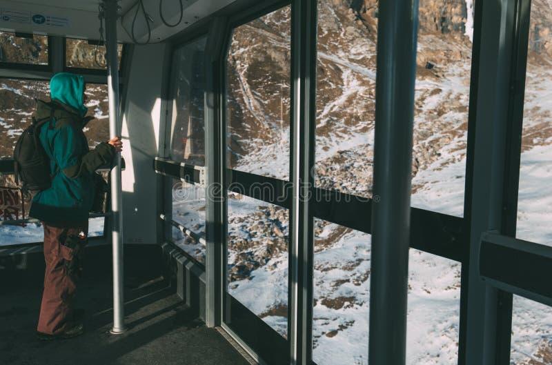 Mens die in skiliftcabine, op metaalbar houden, die uit het venster kijken royalty-vrije stock afbeeldingen