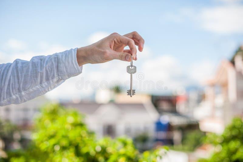 Mens die sleutel houden aan het huis op achtergrond van huizen in de stad Behandel het onroerende goederenconcept stock foto's