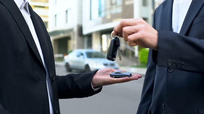 Mens die sleutels voor nieuw vervoer ter beschikking nemen, kopend voertuig, symbolische stuk speelgoed auto stock afbeeldingen
