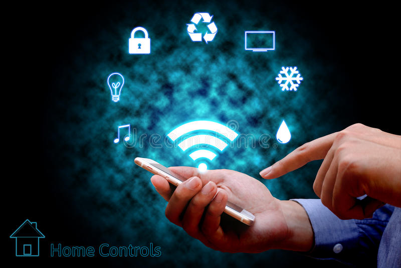 Mens die slimme telefoon of verre huiscontrole gebruiken online huisautomaat stock afbeeldingen