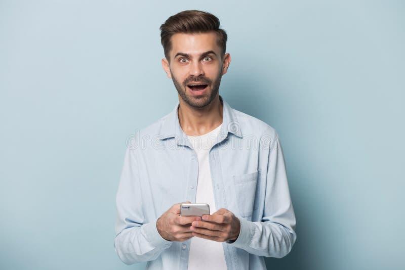Mens die smartphone bekijken die van de cameraholding verbazing voelen stock afbeelding