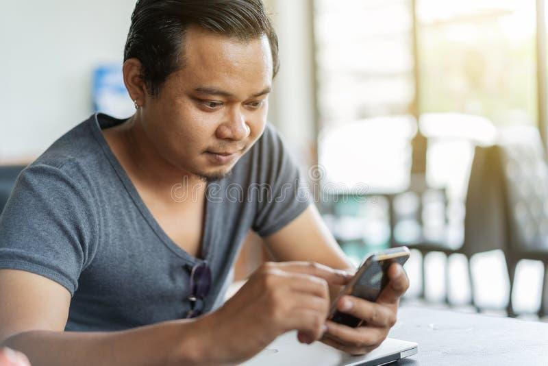 Mens die smartphone in een koffie gebruiken stock foto's