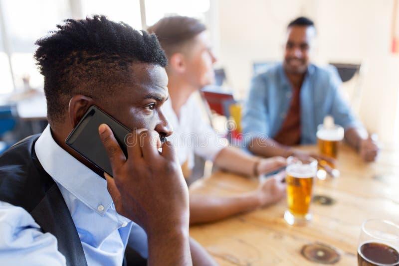 Mens die smartphone uitnodigen en bier drinken bij bar stock afbeeldingen