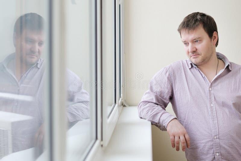 Mens die sneeuw in het venster bekijken stock foto
