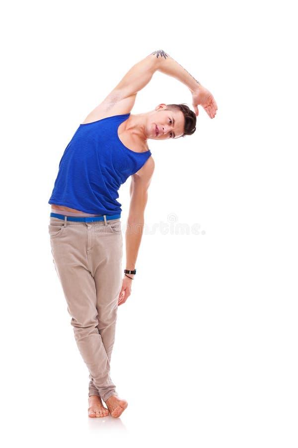 Mens die sommige uitrekkende oefeningen doet stock foto