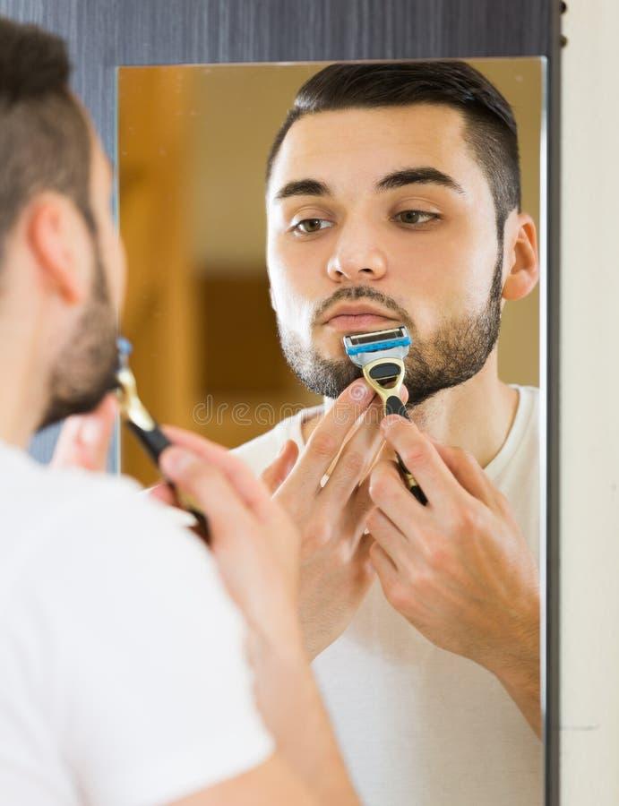 Mens die spiegel en het scheren gezicht met scheermes bekijken stock foto