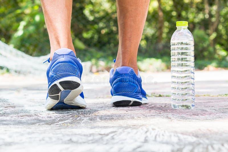 Mens die sportschoenen dragen die in het park met drinkwater lopen stock fotografie