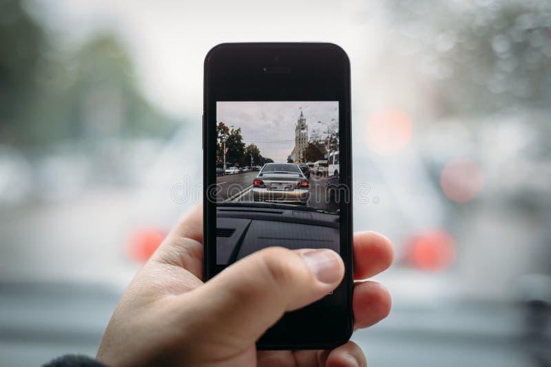 Mens die stadsverkeer schieten door smartphone ter beschikking van zijn gestemde auto, stock foto