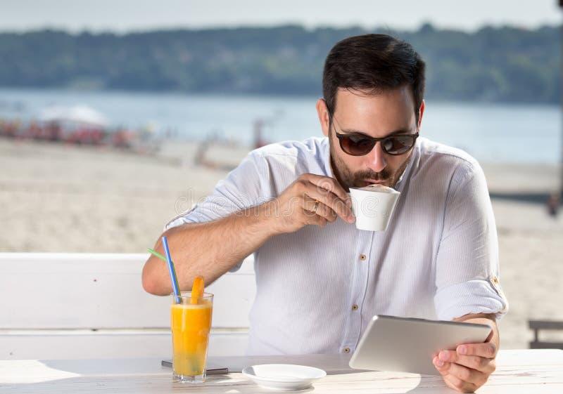 Mens die in strandkoffie genieten van royalty-vrije stock fotografie