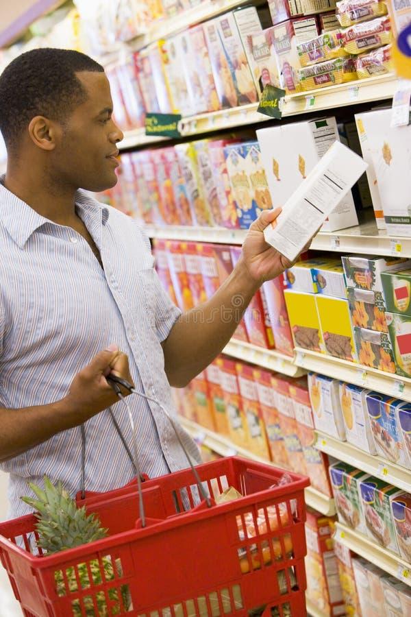 Mens die in supermarkt winkelt stock foto