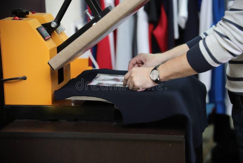 Mens die t-shirt voor druk in de machine van de serigrafiedruk voorbereiden Slechts handen royalty-vrije stock foto's