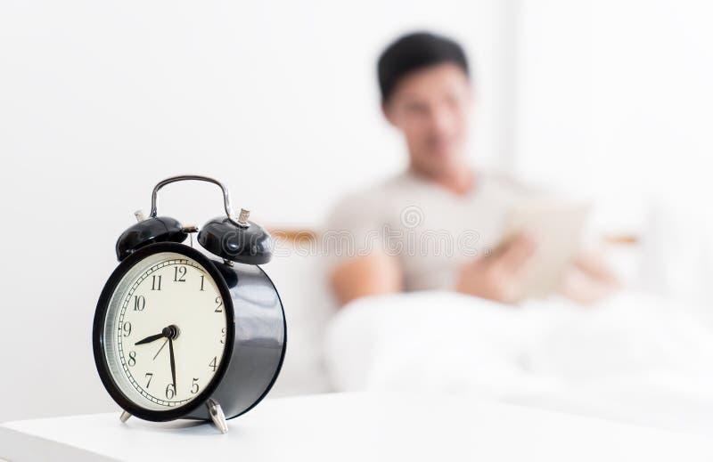 Mens die tablet in bed met wekker gebruiken die laat tellen royalty-vrije stock afbeelding