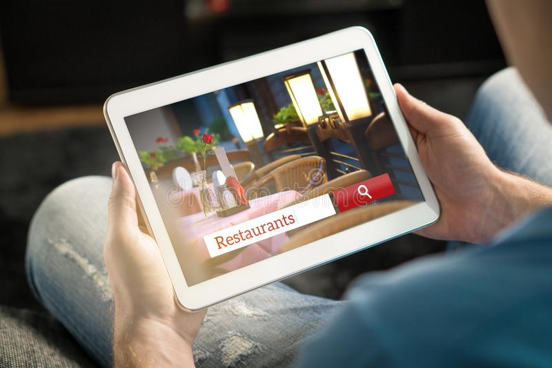 Mens die tablet gebruiken die het perfecte restaurant proberen te vinden royalty-vrije stock afbeeldingen