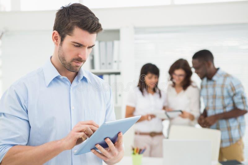 Mens die tablet voor zijn collega's gebruiken royalty-vrije stock afbeeldingen