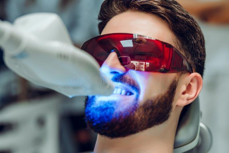 Mens die tanden hebben die door tand UV wittend apparaat, tand hulp behandelende die patiënt, ogen witten met glazen worden besch stock foto