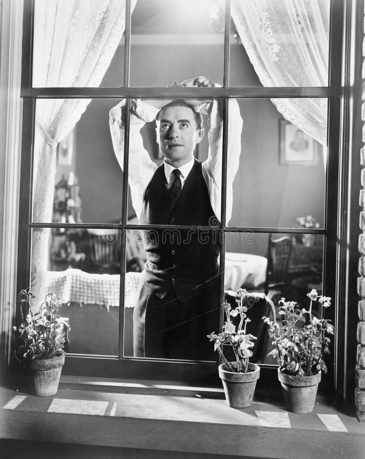 Mens die tegen een venster leunen terwijl dag het dromen (Alle afgeschilderde personen leven niet langer en geen landgoed bestaat stock afbeelding