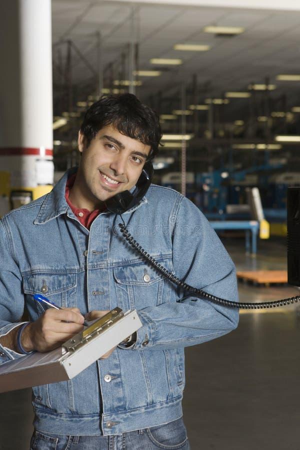 Mens die Telefoon in Fabriek met behulp van stock fotografie