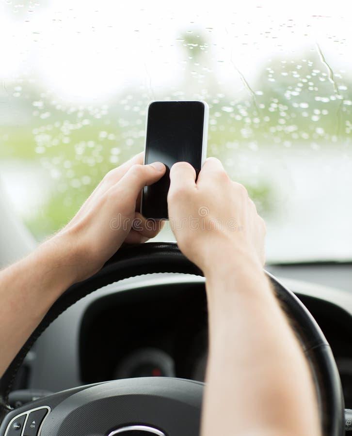 Mens die telefoon met behulp van terwijl het drijven van de auto stock afbeeldingen