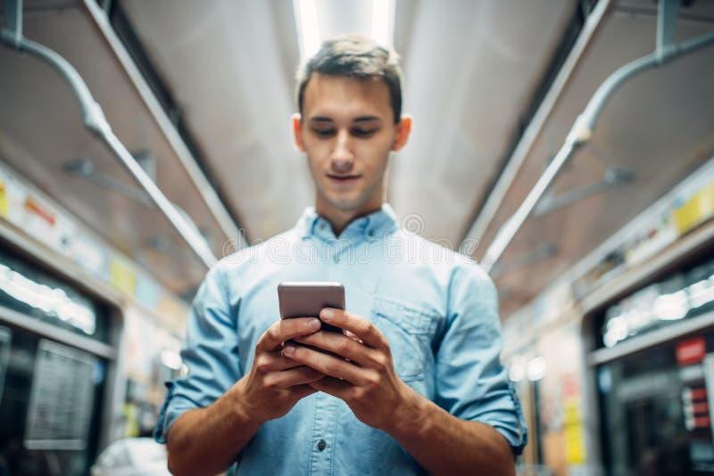 Mens die telefoon in metroauto met behulp van, gewijde mensen stock foto's