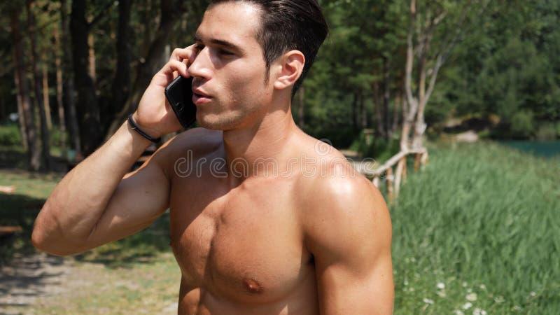 Mens die telefoongesprek maken bij meer royalty-vrije stock fotografie