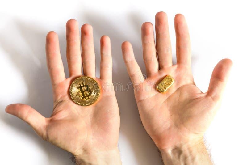 Mens die ter beschikking een gouden bar en een gouden muntstuk Bitcoin houden royalty-vrije stock foto's