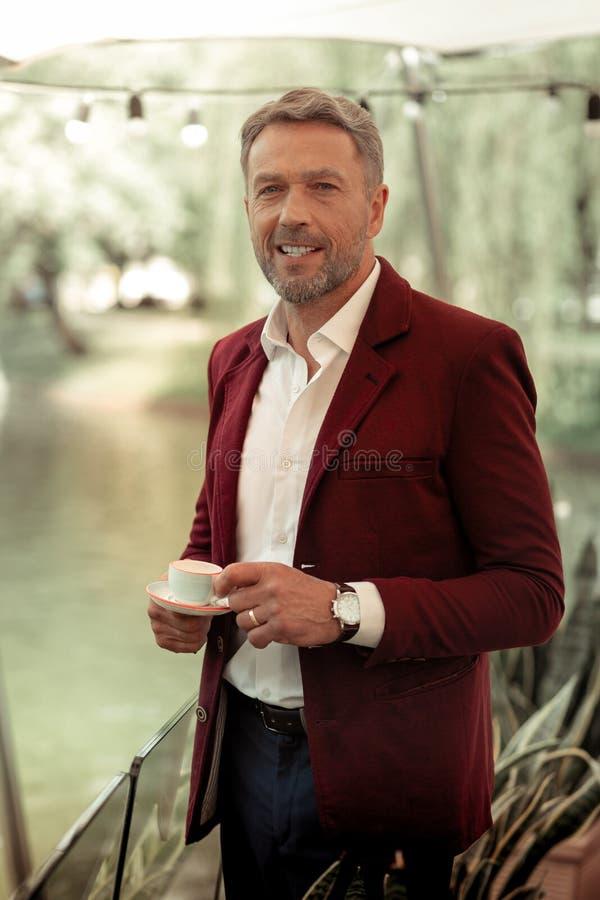 Mens die terwijl het drinken van koffie glimlachen die zich dichtbij meer bevinden stock fotografie
