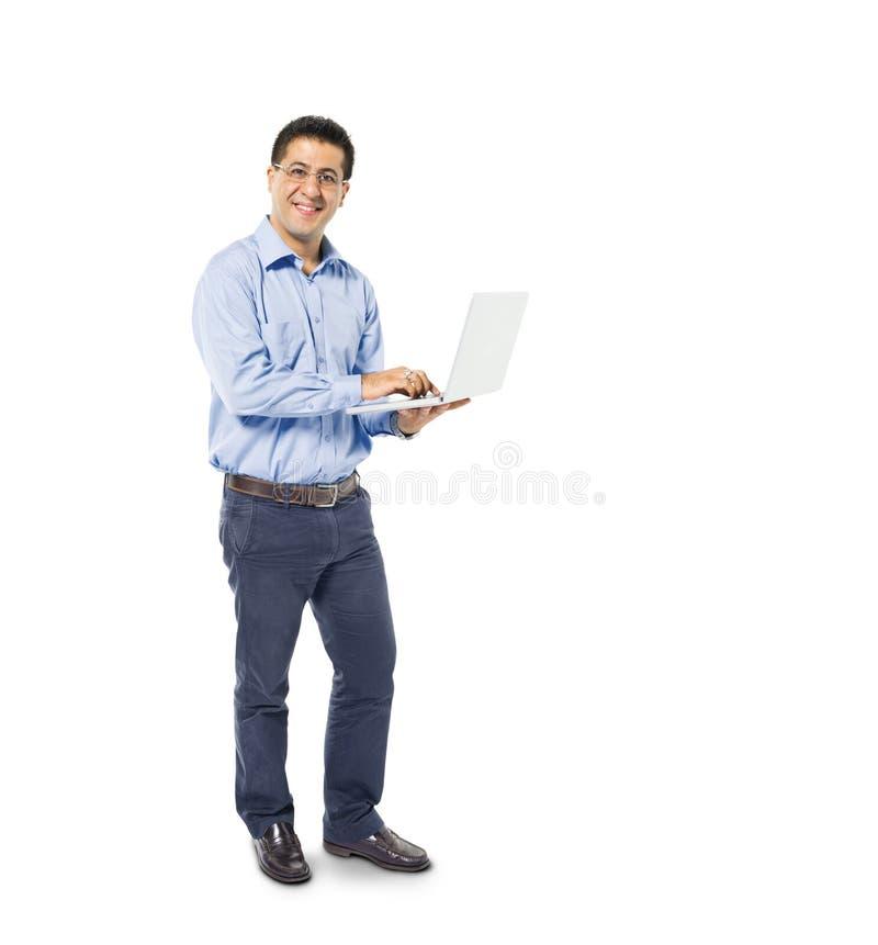 Mens die terwijl het gebruiken van zijn Laptop bevinden zich stock foto's