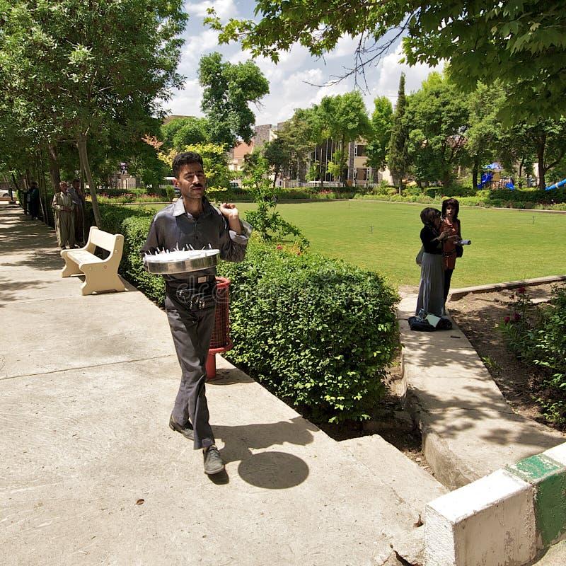 Mens die thee en frisdranken leveren aan zijn klanten in park. Sulaimani, Iraaks Koerdistan, Irak, Midden-Oosten stock afbeelding
