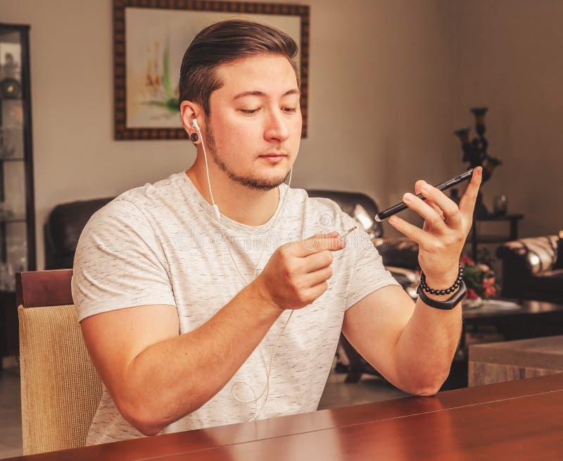 Mens die thuis de oortelefoon op smartphone stoppen stock afbeelding