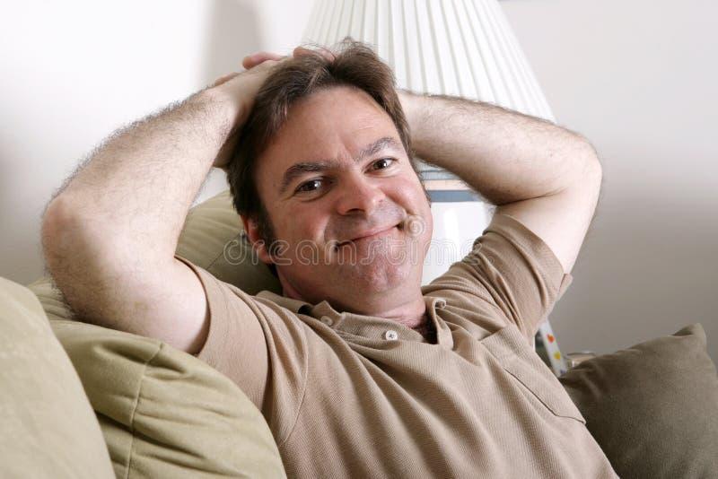 Mens die thuis ontspant stock afbeeldingen