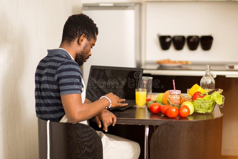 Mens die thuis recept op laptop in keuken kijken stock afbeeldingen