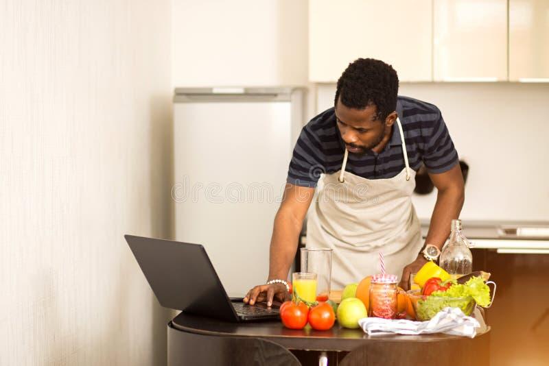 Mens die thuis recept op laptop in keuken kijken royalty-vrije stock afbeeldingen