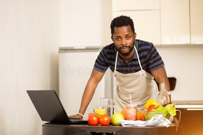 Mens die thuis recept op laptop in keuken kijken royalty-vrije stock foto's