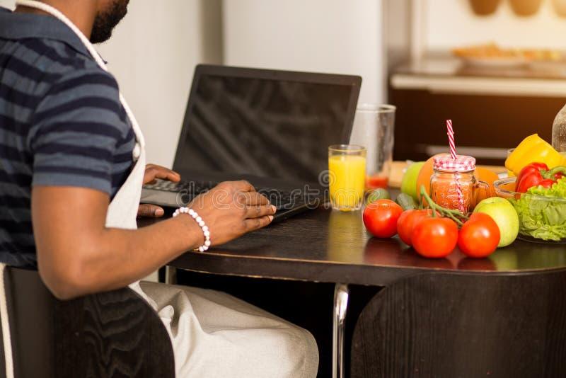 Mens die thuis recept op laptop in keuken kijken stock foto
