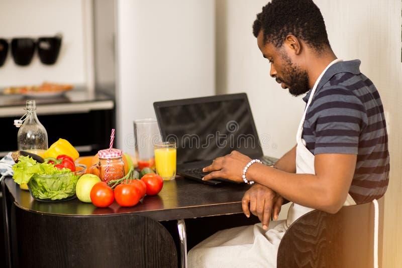 Mens die thuis recept op laptop in keuken kijken stock afbeelding