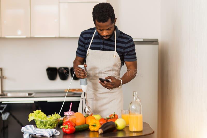 Mens die thuis recept op telefoon in keuken kijken royalty-vrije stock foto