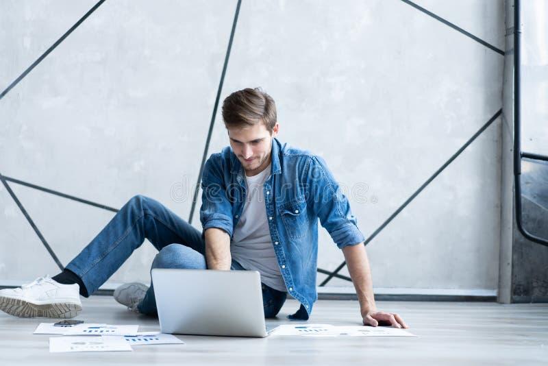 Mens die thuis werkt Knappe jonge mensenzitting op de vloer en het onderzoeken van document terwijl laptop en documenten het legg stock fotografie