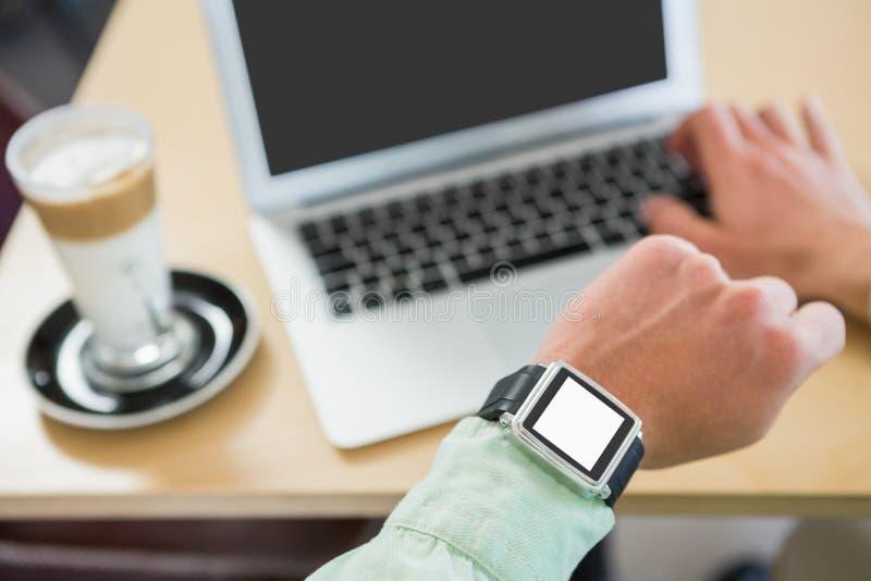 Mens die tijd controleren op zijn smartwatch stock foto