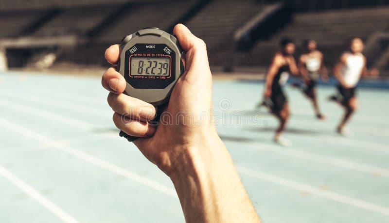 Mens die tijd houden bij een lopend ras die chronometer gebruiken royalty-vrije stock afbeelding