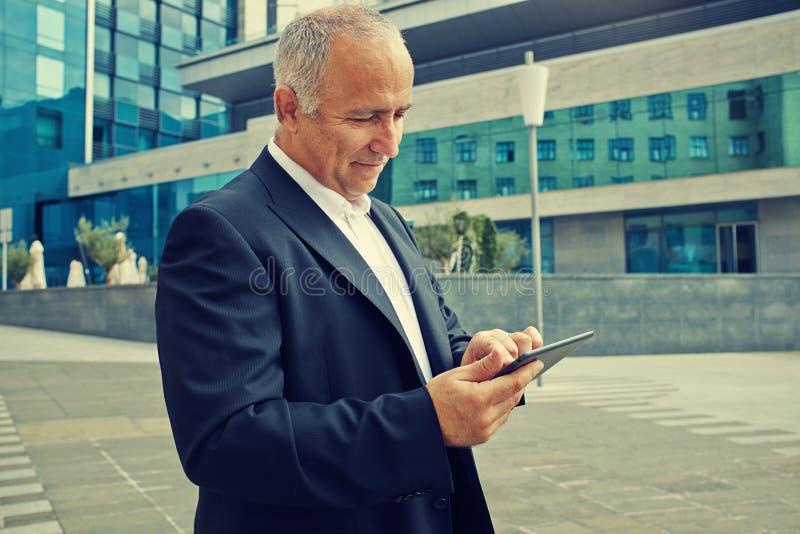 Mens die touchpad bij openlucht gebruiken stock fotografie