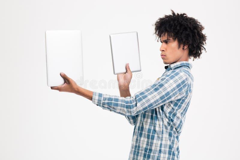 Mens die tussen tabletcomputer of kleine laptop kiezen stock foto